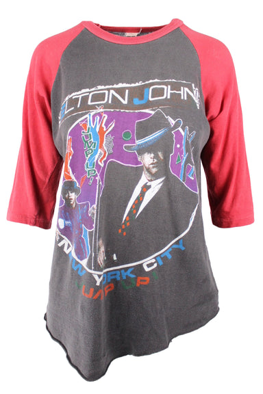 vintage elton john tee from the madison square garden show of their jump up! tour in the 80s. baseball style tee with washed charcoal body and washed red 3/4 sleeves. featuring elton john graphics on front and back. rolled bottom hem.