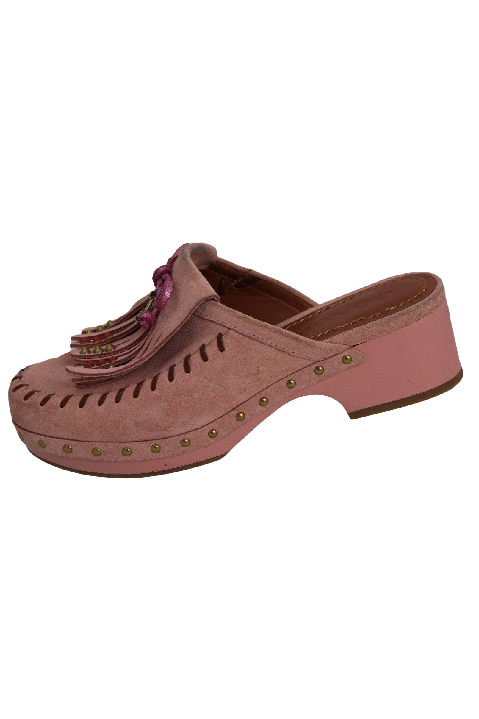 coach pink clogs. features pink bow at tongue with gold tone charms attached, fringe, red and gold tone studs throughout with brown stitch details and a tonal chunky heel.