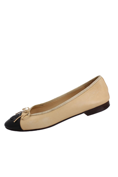 chanel pale coral ballet flats. features black toe box with brand name logo & ribbon at toe box.