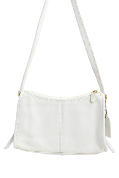 coach white shoulder bag. features a zipper closure & an internal pocket.