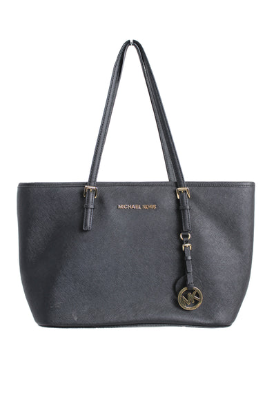 michael kors black purse. features several pockets for storage & zipper closures.