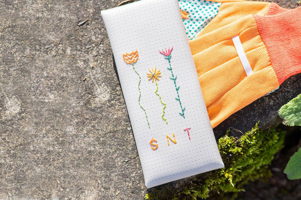 Birth flowers stitched onto the Envelope case by Chasing Threads