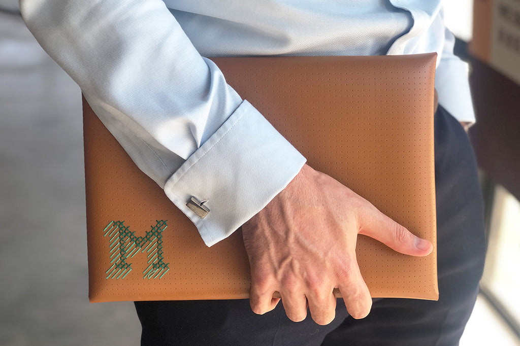 man carrying brown stitched laptop case with M 3D initials stitched in green and teal