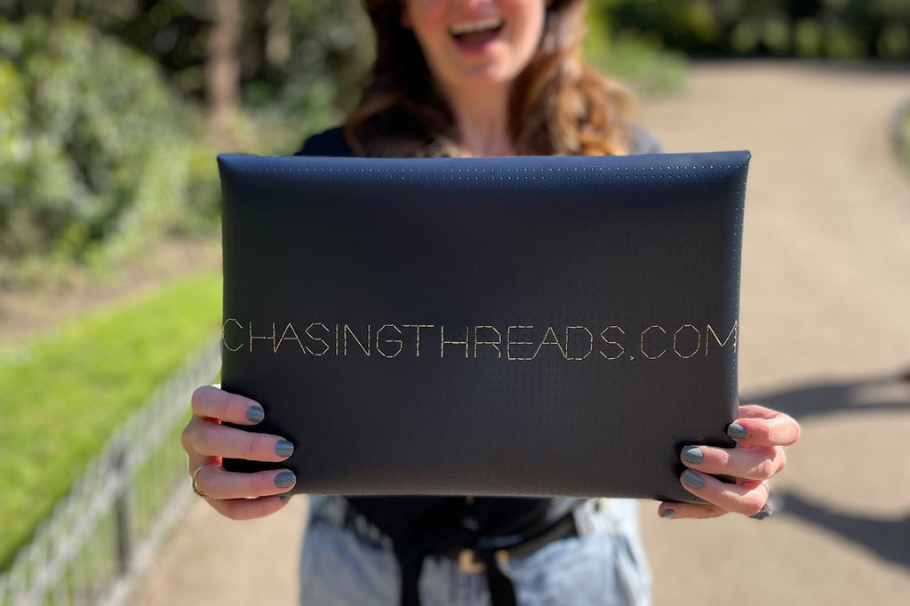 chasingthreads.com stitched on navy laptop sleeve