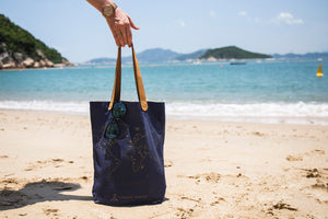 Navy stitch tote bag at beach. Travel bag perfect for recording your travels with cross-stitches