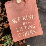 """We Rise By Lifting Others"" Tee - Heather Mauve"