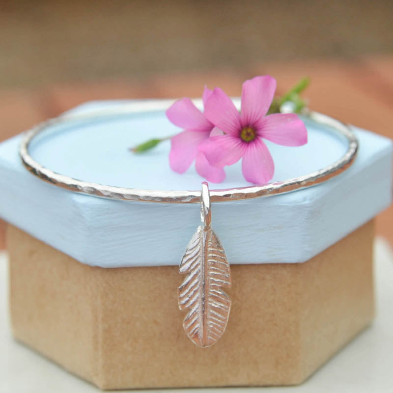 Silver stacking hammered bangle with feather charm