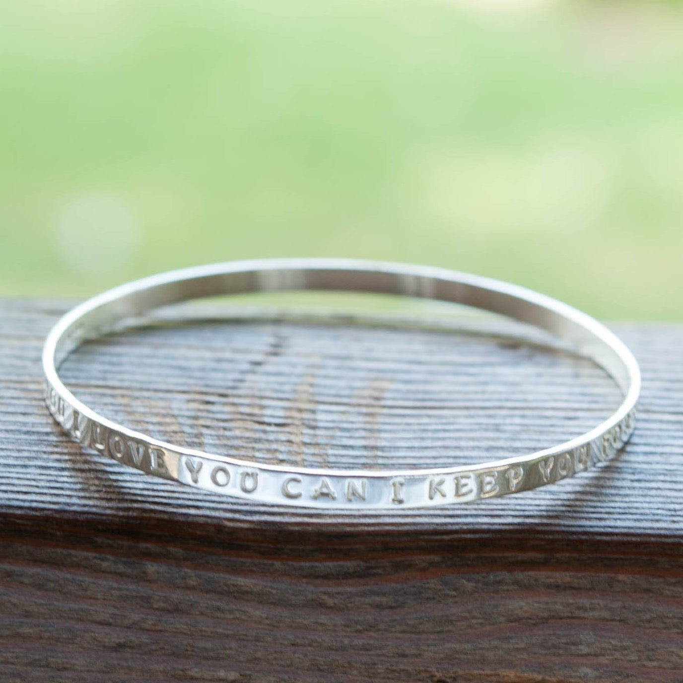engraved silver message bangle with a quote about love