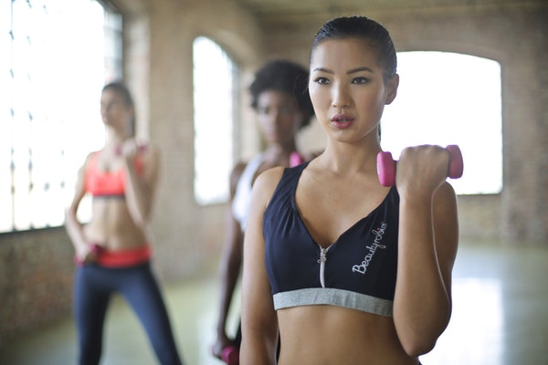 Eve and Elle woman working out with weights in exercise class