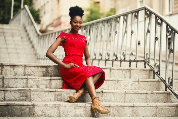 Eve and Elle woman in red dress sitting on stairs smiling