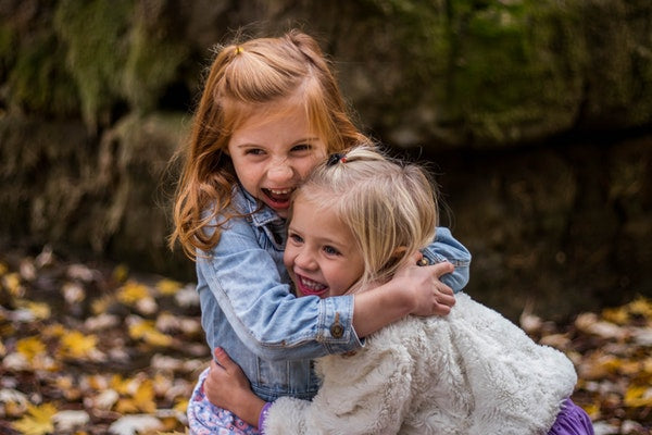 eveandelle two girls plaing outside smiling having fun hugging in leaves