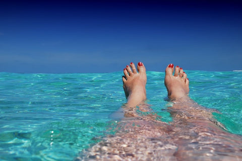 Woman's legs stretching out in tropical clear blue water with red painted toenails
