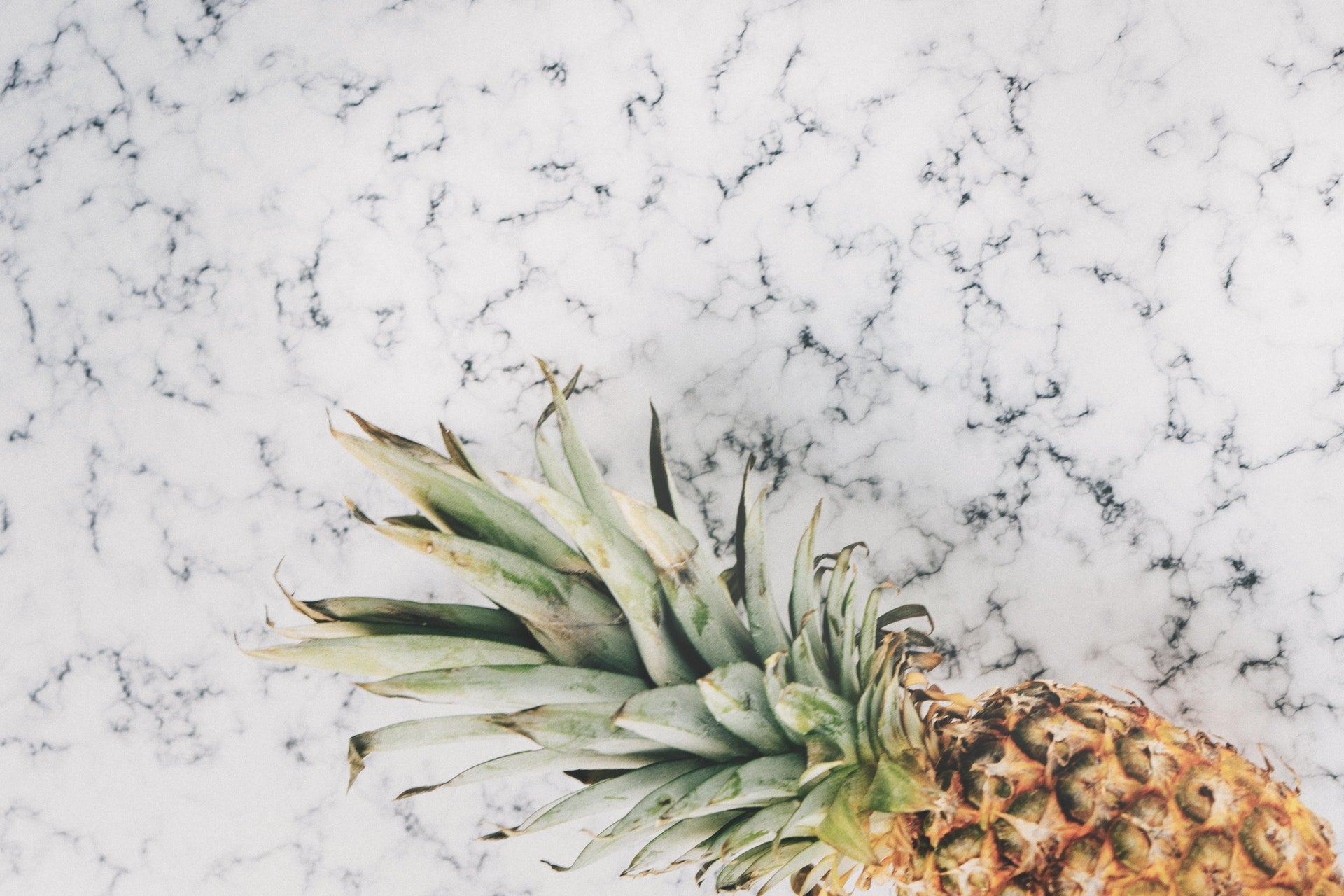 pineapple on marble counter background flat lay eveandelle