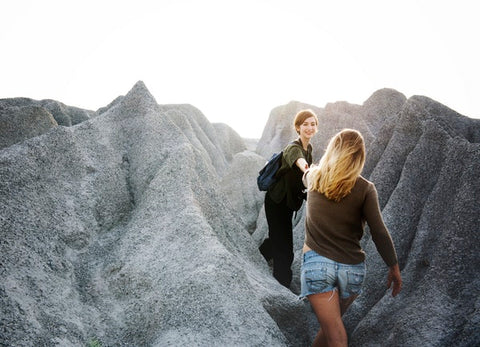 Brunette woman reaching out hand to help other blond woman to climb a mountain