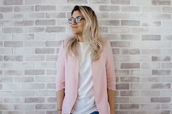 Blond woman with glasses in pink blazer smiling