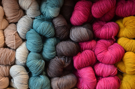colorful hand-dyed yarn skeins in lavender, turquoise, grey, hot pink, mustard
