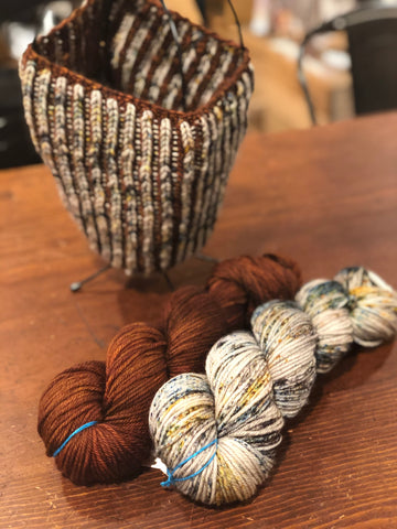 Shown: A two-color brioche cowl knit in a warm cocoa brown and speckled cream with woodsy tones; the two skeins of yarn are shown in front