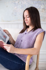a brunette wearing a lavender button-down knitted vest relaxes on a chair, reading a book