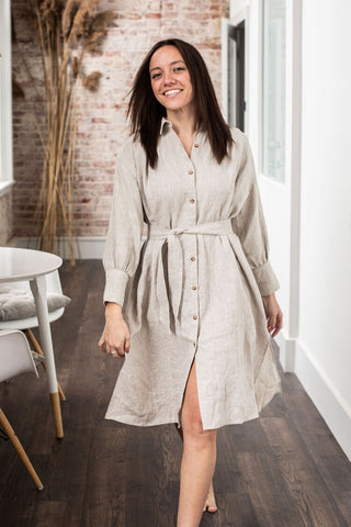 a brunette wearing a belted loose-fitting shift dress in light oatmeal color strides confidently toward the camera