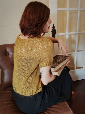 A woman with mid-length reddish-brown hair sits on a leather sofa, wearing black pants and a Ranunculus top (designed by Midori Hirose) knit in Shibui Knits Silk Cloud held together with Cima, color: Pollen