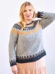 Blond woman wearing Stowe: A modern colorwork yoke pullover with an Icelandic-inspired motif in grey, yellow, and charcoal; designed by Amy Christoffers in Berroco Mochi
