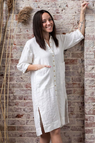 a brunette with one hand in the pocket of her loose-fitting white shift dress leans against a whitewashed brick wall