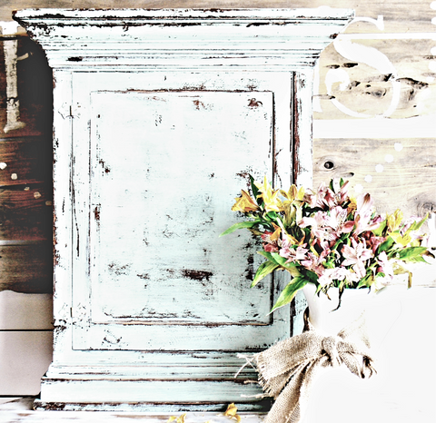 White, chippy cabinet with faded flowers in a vase.
