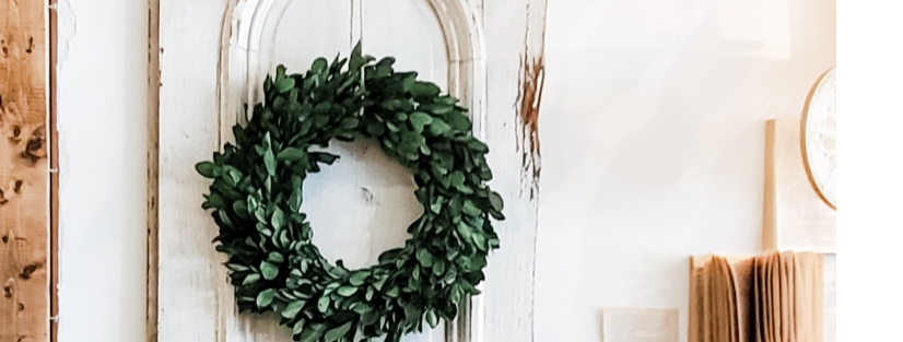 Boxwood wreath hanging on chippy white door
