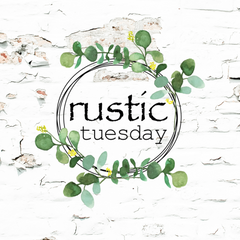 rustic tuesday logo over a white painted, chippy brick wall
