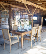 barn setting with table,chairs and rustic light fixture made of metal, wood and screen shades