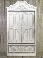 Large, ornate and heavily detailed armoire painted in Rethunk Junk by Laura Paint in the color Cotton, which is a warm white.