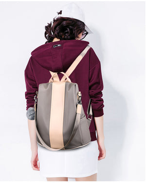 Woman is wearing khaki anti theft backpack
