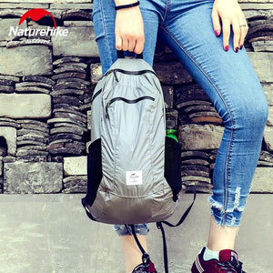 Woman holding NatureHike Packable Backpack 18L - Grey