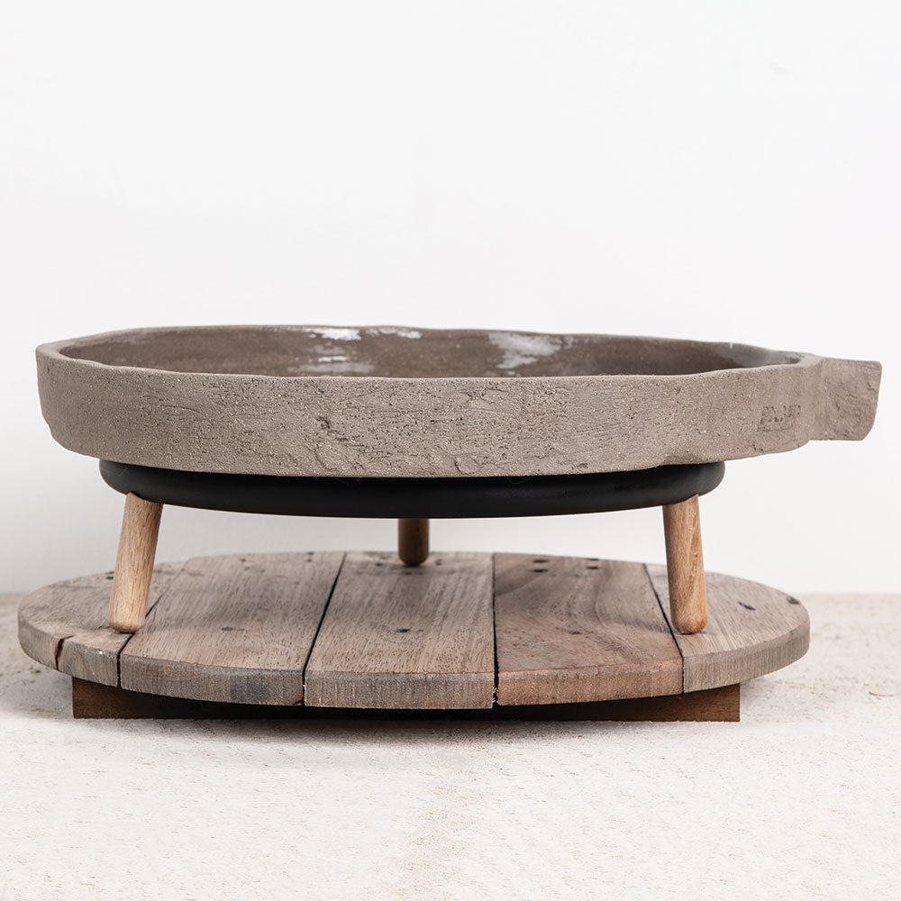 Grey, concrete designer plateau/platter from Serax for Olea Living. Round with glazed top and rough base, straight edge handle to side. With round wooden bowl carrier and round wooden board.