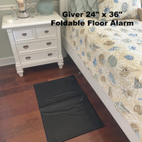 "Giver 24"" x 36"" foldable floor alarm shown alongside a bed"