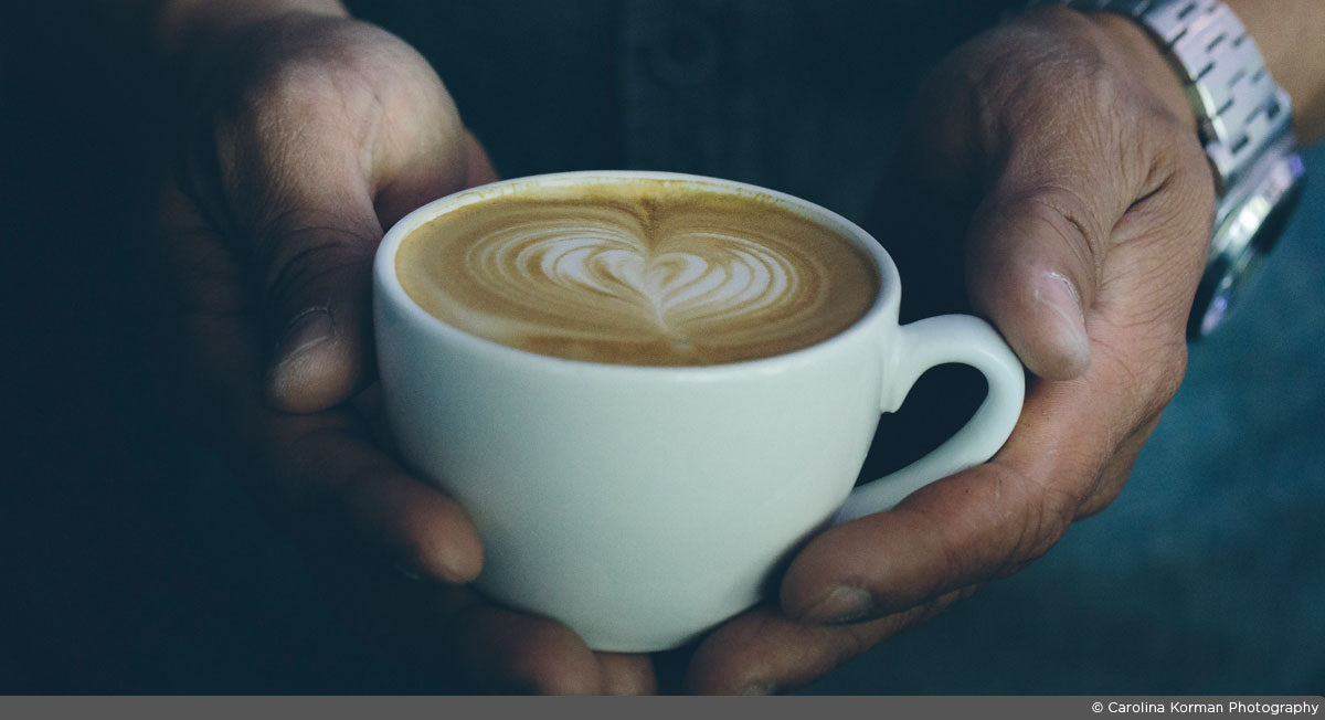two hands holding a cappuccino in a white cup with heart latte art