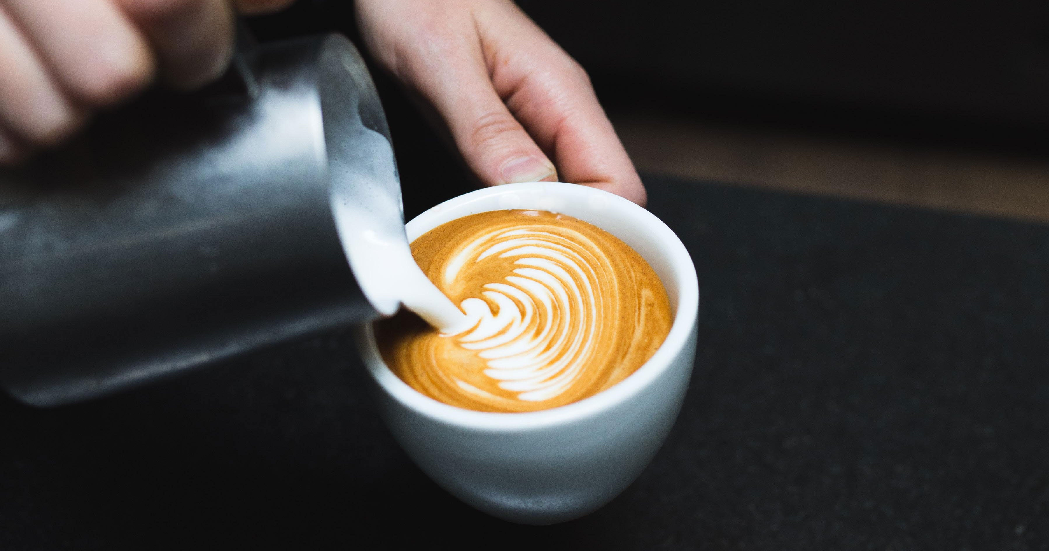 rosetta latte art being poured into a white cup