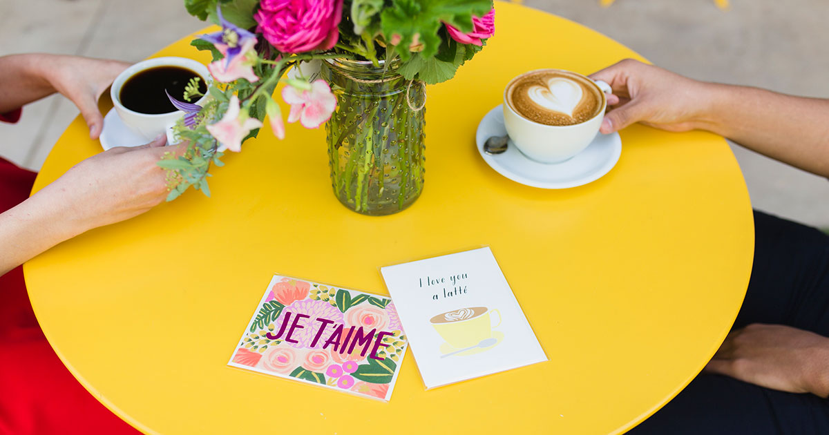 two people sitting opposite each other at a yellow table, each holding a cup of coffee, while two greeting cards sit between them