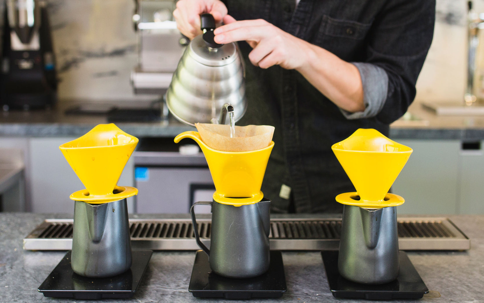 three sets of yellow bee house drippers, and black 20oz steaming pitchers sit in a row as a person brews coffee in the middle set, while pouring from a chrome hario v60 kettle