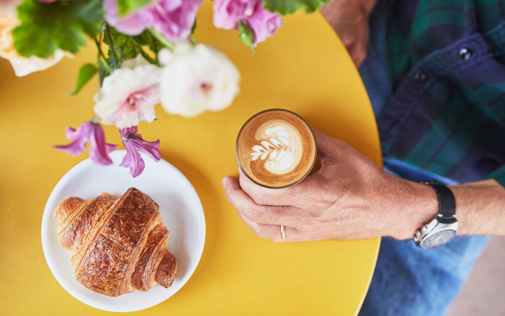 a person seated at a yellow table holding a gibraltar with rosetta latte art. a croissant on a plate sits at the table as well.