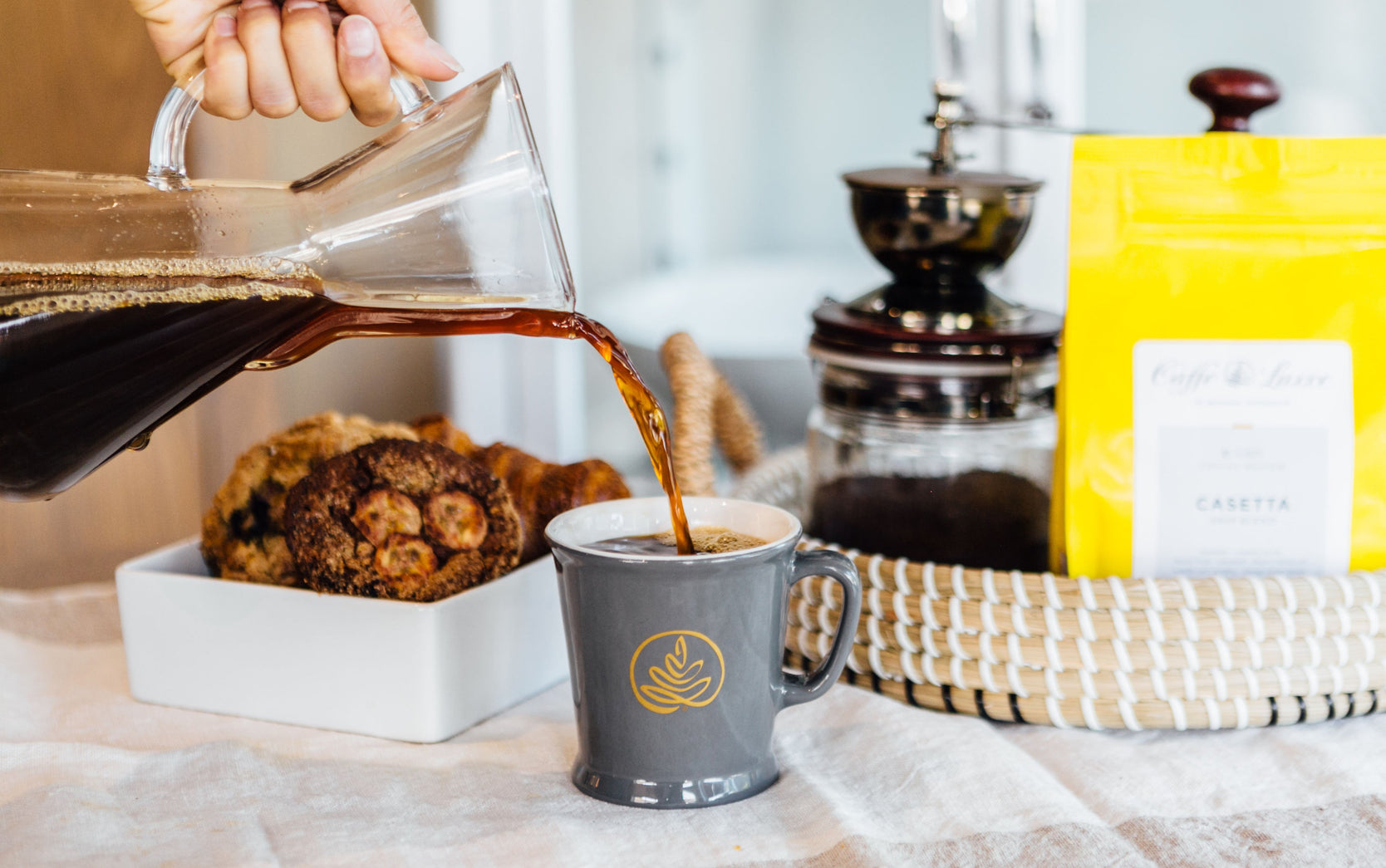 coffee being poured from a small 1 - 3 cup chemex into a grey mug, which bears a caffe luxxe logo in gold. in the background are pastries, a bag of coffee, and a manually operated grinder.