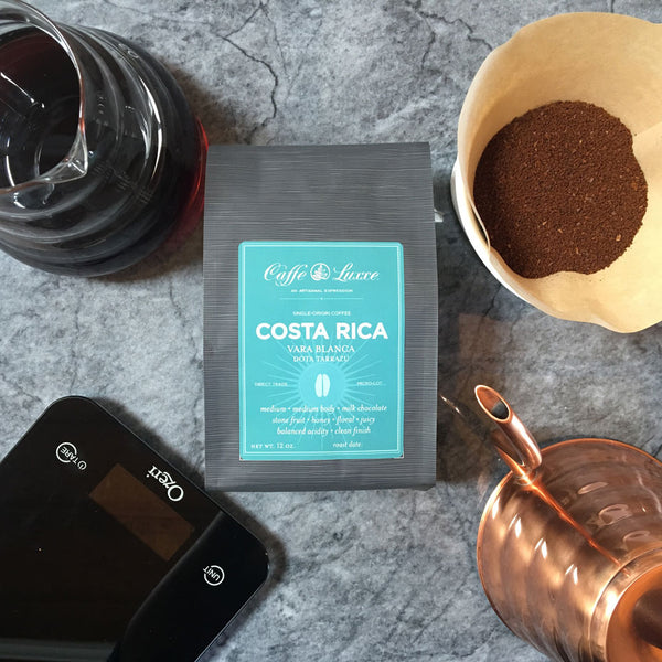 a bag of caffe luxxe costa rica vara blanca surrounded by various coffee brewing equipment