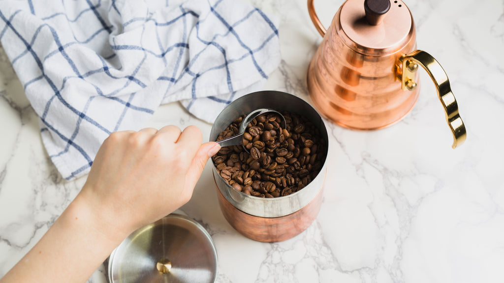 a hand scooping coffee out of copper canister