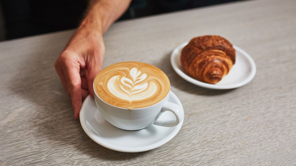 latte with rosetta latte art and croissant on a light grey colored table