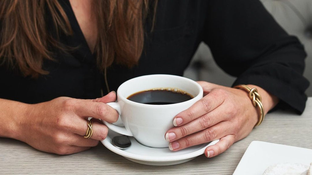 woman sitting with cup of coffee in front of her