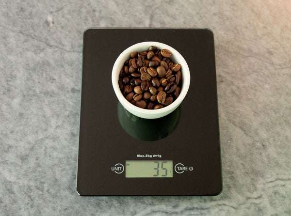 coffee being weighed on a black scale on scale