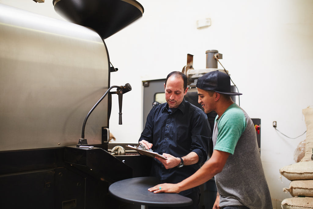 two roasters in front of a roasting machine