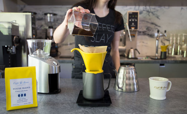 a woman dosing coffee into pour over
