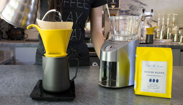 a woman making pour over coffee next to a  burr grinder and a bag of coffee