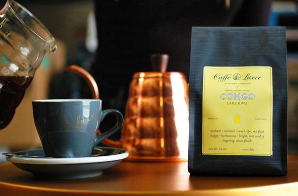 a bag of congo coffee from caffe luxxe next to a coffee cup with coffee about to be poured into it
